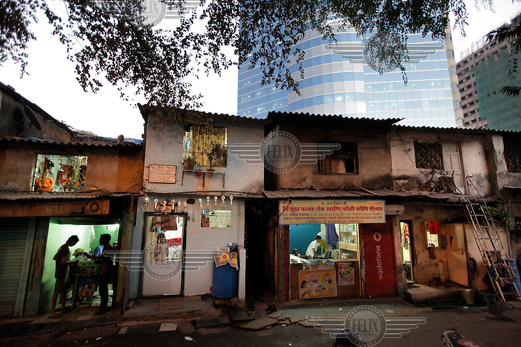 Shops and crumbling old slum buildings  in front of a modern office building in the Arya Nagar area of Mumbai.
