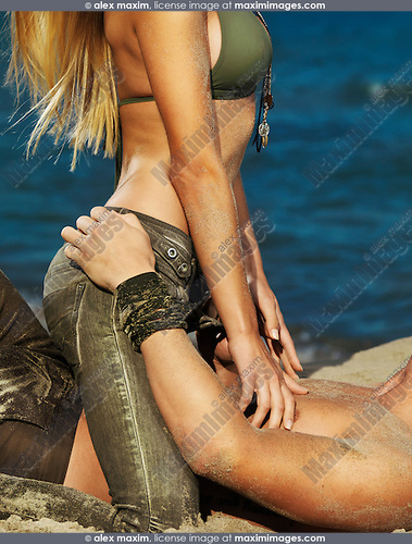 Sensual portrait of a sexy young couple making love on sand at the beach