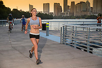 Beautiful young woman running on the Boardwalk Trail along Lady Bird Lake as the sun sets on the booming downtown Austin, Texas Skyline.