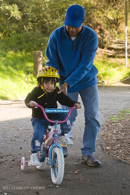 Berkeley CA  Adoptive father teaching Guatemalan daughter, three and a half, how to ride bike  MR