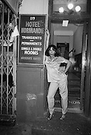 May, 1980. Manhattan, New York City, NY. A prostitute stands in the doorway of the long since closed Hotel Normandie. Only a couple of the classic Times Square &lsquo;flop houses&rsquo; remain, where a guest can rent a room for the night, or by the hour if need be. <br /> <br /> Manhattan, New York City, NY. Mai, 1980.1 heure du matin : Une prostitu&eacute;e au sourire engageant devant le Normandie, un h&ocirc;tel de passe qui depuis  a &eacute;t&eacute; d&eacute;clar&eacute; insalubre et a &eacute;t&eacute; d&eacute;moli.