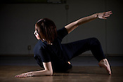 Portraits of a young Japanese female doing yoga in a dimly lit studio.