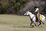 A cowboy galloping full speed in a Texan field in fall