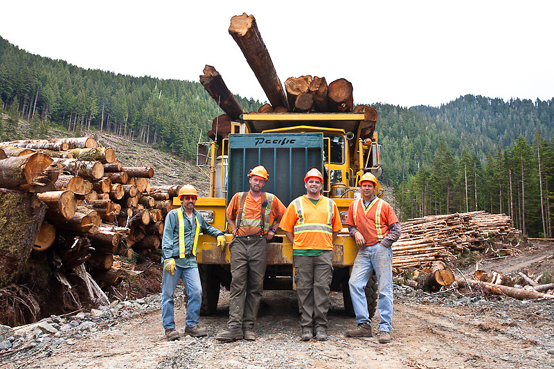 Chris Warren (log truck driver), John Orton (landing bucker), Ryan Ricard (Forestry Engineer, Interfor), Glen Kappel (Logging Manager, Olympic Forest Products) indulge the photographer in front of a loaded logging truck in the middle of a second growth clear cut. Prior to interest from China, there was little or no market for the logs coming from this region. Chamiss Bay, Vancouver Island, July 2012.