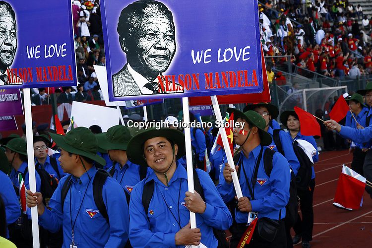 PRETORIA - 13 December 2010 - The Vietnamese delegation to the 17th World Festival of Youth and Students carry posters of Nelson Mandela as they march through the Lucas Moribe stadium at the start of the festival. -- APP/Allied Picture Press