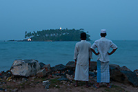 Tamil (Muslim) villagers look out to Barberyn (Beruwala) light at twilight -Beruwala, Sri Lanka