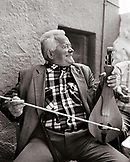 GREECE, Patmos, Diakofti, Dodecanese Island, a happy Greek man plays the Lyra at Diakofti Taverna (B&W)