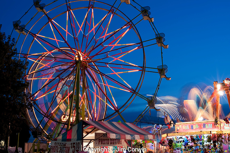 Evergreen State Fair at twilight with Ferris Wheel and amusement rides and game booths at night Monroe Washington State USA