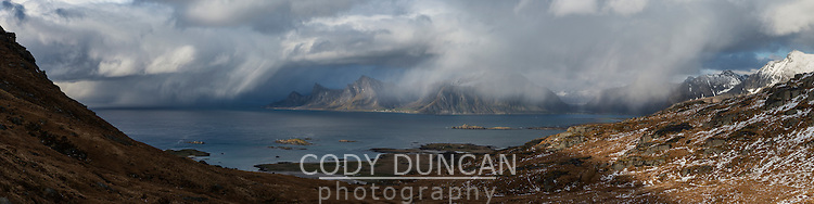 Spring snow flurries pass over Flakstadøy, from near Ryten, Moskenesøy, Lofoten Islands, Norway