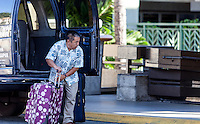 Local Asian male shuttle van driver unloading luggage at the Honolulu International Airport, O'ahu