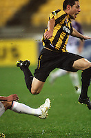 Phoenix' Leo Bertos leaps over a tackle attempt during the A-League football match between Wellington Phoenix and Perth Glory at Westpac Stadium, Wellington, New Zealand on Sunday, 16 August 2009. Photo: Dave Lintott / lintottphoto.co.nz