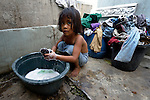 "In the capital of the Philippines, 5-year old Claris Caralos washes clothes in the Manila North Cemetery. Hundreds of poor families live here, dwelling in and between the tombs and mausoleums of the city's wealthy. They are often discriminated against, and many of their children don't go to school because they're too hungry to study and they're often called ""vampires"" by their classmates. With support from United Methodist Women, KKFI provides classroom education and meals to kids from the cemetery--including this girl--at a nearby United Methodist Church."