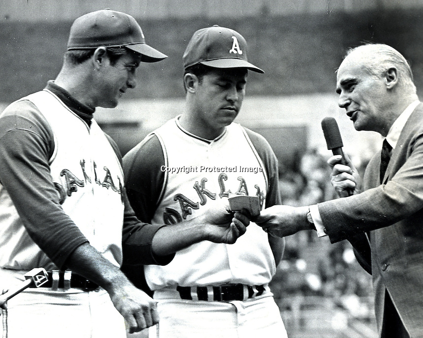 "Oakland Athletics owner Charlie Finley gives bonus checks to A's Jim ""Catfish"" Hunter and catcher Jim Pagliaroni after Hunters perfect game. (1968 photo by Ron Riesterer)"