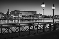 Slottet i djup skymning sedd från Skeppsholmsbron med lyktor i Stockholm i svartvitt