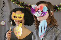 NWA Democrat-Gazette/DAVID GOTTSCHALK Karmyn Clark (left), a sophomore at the University of Arkansas, and Mac Rex, a freshman, pose with masks Monday, February 12, 2018, during the Beads and Bling It's a Mardi Gras Thing in the Arkansas Union International Connections Lounge on the campus in Fayetteville. The celebration, hosted by University Programs, offered King Cake, mask decorating, trivia and other activities.