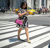 A pedestrian checks her smartphone while crossing a Fifth Avenue intersection in New York on Friday, May 27, 2016. (© Richard B. Levine)