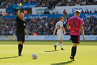(L-R) Referee Kevin Friend shows a yellow card to Jake Bidwell of Queens Park Rangers during the Sky Bet Championship match between Swansea City and Queens Park Rangers at the Liberty Stadium, Swansea, Wales, UK. Saturday 29 September 2018