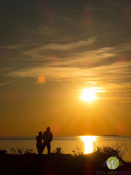 Hammonasset State Beach Park. Long Island Sound. Sunset. Silhouetted couple watching sunset.