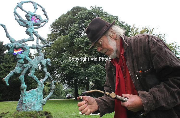 """Foto: VidiPhoto..OOSTERBEEK - Voor het Airborne Museum Hartenstein in Oosterbeek is maandag een enorm bronzen beeld van de bekende kunstenaar Jits Bakker (foto) geplaatst.  Het kunstwerk, met de naam """"We'll meet again"""" is een cadeau van het Nederlandse volk aan de geallieerde 'bevrijders' die hebben deelgenomen aan de (mislukte) operatie Market Garden (1944). Het beeld staat daarom in Oosterbeek totdat er in Londen een geschikte plek voor is gevonden. Het 6 meter hoge kunstwerk is door Jits Bakker kosteloos gemaakt ter nagedachtenis aan de legendarische Slag om Arnhem en symboliseert een landende parachutist die door het uitzinnige volk wordt opgevangen als bevrijder. Bakker heeft als zevenjarig jongetje de operatie Market Garden van dichtbij meegemaakt.."""