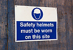 A3A9G5 Safety helmets must be worn blue and white poster on a building site