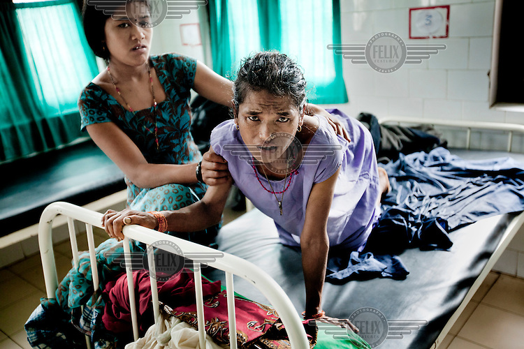 35 year old Santa Maya Rumba kneels on a bed during her labour. She travelled by foot and by bus to get from her mountain home to the maternity hospital. A state program has been instigated to enable women to have hospital births instead of home births and thereby reduce infant and maternal mortality rates at birth.