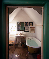 This small attic bathroom has whitewashed walls and is simply furnished