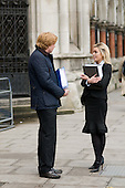 A man and a woman holding legal files talk outside the Royal Courts of Justice, London