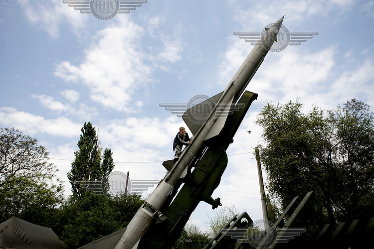 11 year old Artem climbs on a Soviet era missile in a military park.