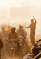 A policeman controls traffic on a main road. Thousands of people ride in the mornings on their mopeds, a time called Moped Mania, in Bamako, Mali