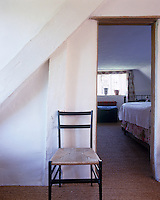 A lone chair stands sentinel at the doorway to an attic bedroom