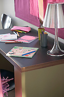 Detail of a child's colouring books and pencils on top of a desk in the bedroom