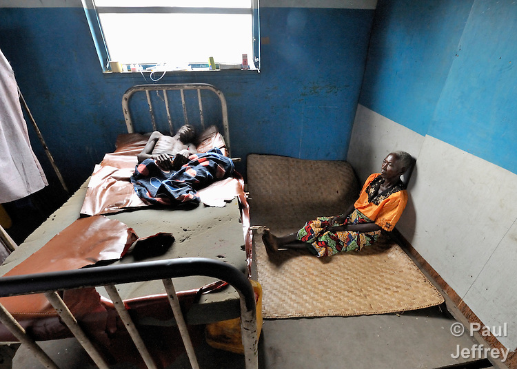 A woman sits by the bedside of her ill husband in the United Methodist Hospital in the village of Wembo Nyama, DR Congo.