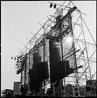 Grateful Dead Live at Dillon Stadium featuring the Wall of Sound. Hot summer sun setting behind the scaffolding. Note the roadie on the rigging. This shot taken just before the start of the show which was at 6pm. In Hartford, CT on July 31, 1974.