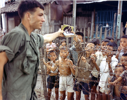 "Saigon, Vietnam - August 1, 1968 -- Private First Class (PFC) Mark W. Howard of Detroit, Michigan, a rifleman with the United States Army Company ""A"", Third Batallion, 7th Infantry, 199th Light Infantry Brigade, buys a magazine from a Vietnamese child in Saigon, Vietnam on August 1, 1968..Credit: Burt W. Peterson - U.S. Army via CNP"