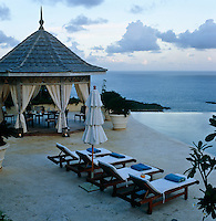 Clouds gather on the horizon as the sun goes down over the infinity pool and its dining gazebo