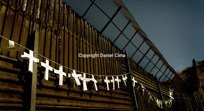 Crosses displayed at the border fence with the names of people who died trying to cross the Arizona desert..Nogales, Mexico Nov. 2007