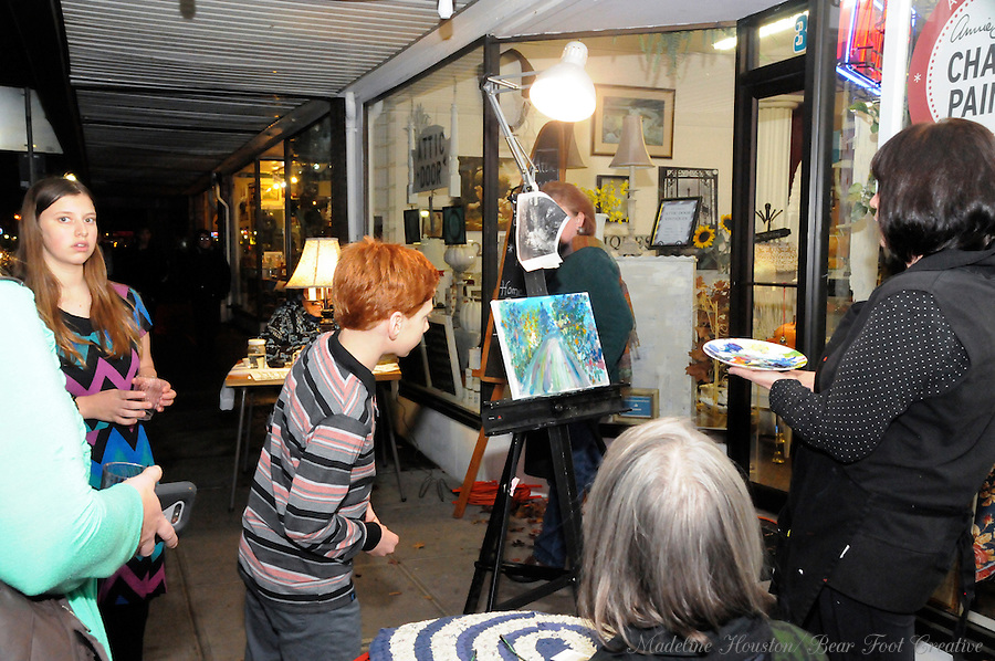 Artist Sue Wachter participates in the fall scene paint-off, organized by the Rectangle Gallery, and Grace Willis demonstrates her toothbrush rug art in front of The Attic Door during Centralia, Washington's Third Thursday on October 20, 2016.