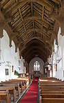 View down the church nave over wooden pews to the altar and east window. The hammer beam roof with carved angels was  thought by H Munro Cautley to be the most perfect example of a single hammerbeam in England.  Badingham, Suffolk, England, UK