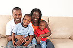 Portrait of family at home sitting on couch parents and sons ages 3 and 12 months old horizontal