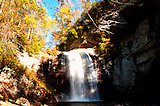 Wide landscape view of Looking Glass falls, rocks on beautiful fall color