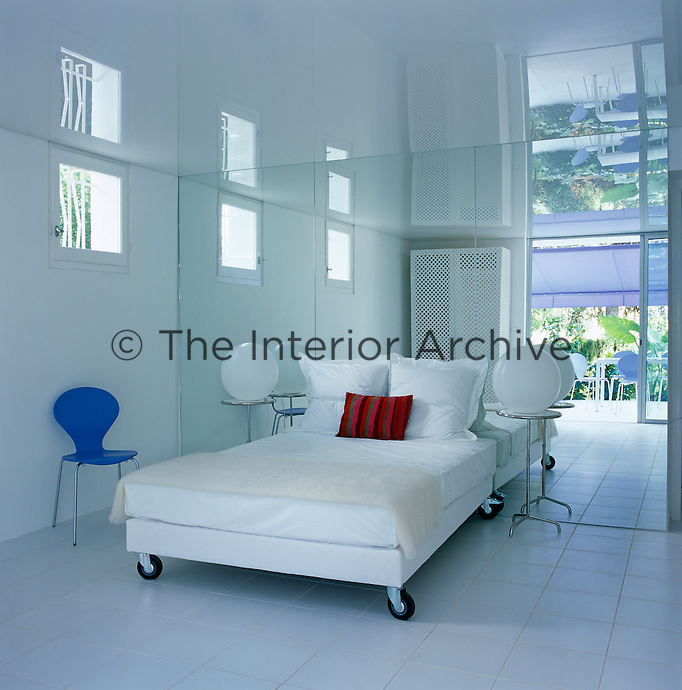This contemporary guest bedroom has a suspended ceiling in clear plastic and a mirror wall behind the bed