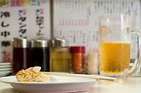 Gyoza, or fried Japanese potsticker dumplings, and a mug of beer make a delicious if unhealthy snack in a Shibuya noodle shop.