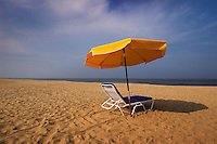 Lounge chair and umbrella sit on the sand at beach