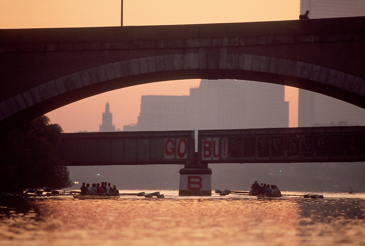Boston, Rowers in eight oared racing shells workout at dawn on the Charles River. Boston city skyline in the distance