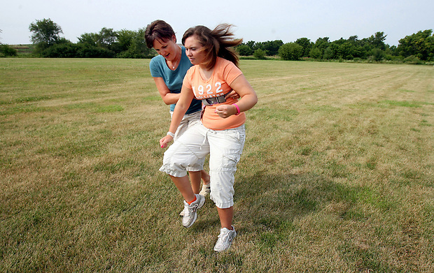 "Elizabeth works on her running stride while physical therapist Shannon Wieland supports her from behind during a therapy session outside On With Life, a brain injury rehabilitation center in Ankeny.  In about eight months Elizabeth has gone a coma to saying, ""I want to run again."""