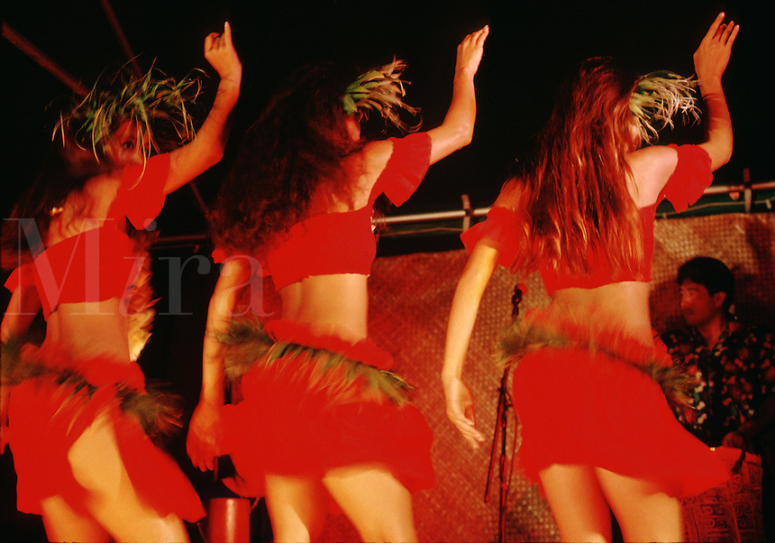 Three female hula dancers seen from behind, in motion, wearing red costumes and ornate headpieces.