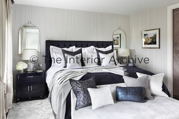 The master bedroom walls have been hung with Ralph Lauren pinstripe wallpaper; a modern nod to Georgian style