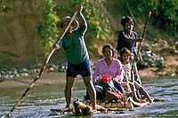 Quechua Indian family from San José de Uchupiamonas travelling on a balsa raft to Rurrenabaque, lowland tropical rainforest along the Rio Tuichi, Madidi National Park, La Paz, Bolivia.