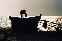 A Goan fisherman fixes his nets in the late afternoon on his traditional outrigger fishing boat, Goa, India.