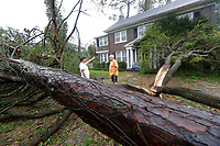 Chris Butcher, of Arborist Plus in Edgewood, Fla., talks with Mike Kiernan, right, about the damage to his home in Wilmington, N.C., after Hurricane Florence made landfall Friday, Sept. 14, 2018. (AP Photo/Chuck Burton)